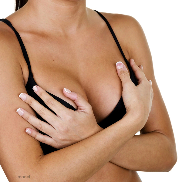 Photo of woman wearing a black bra and holding her breasts. Illustrates the many breast sugical procedures performed at Chicago's Iteld Plastic Surgery